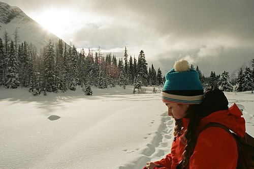 photograph of woman in snow with sun behind. She is wearing a red jacket.