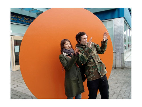 man and woman in front of gold disc