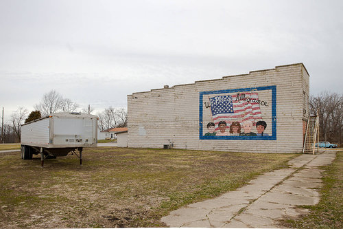 photograph of building with flag and truck container