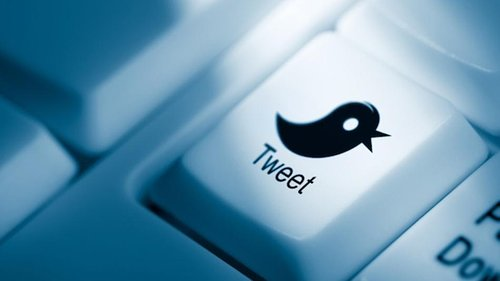 detailed photograph of a keyboard showing a bird on a key that says tweet