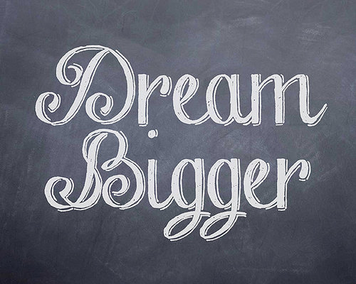 chalk board that say dream bigger written on it