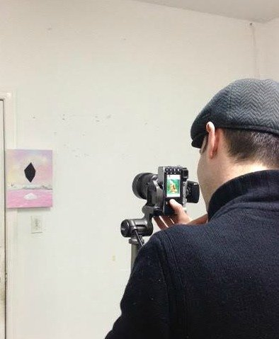 photographer looking through camera at painting on wall