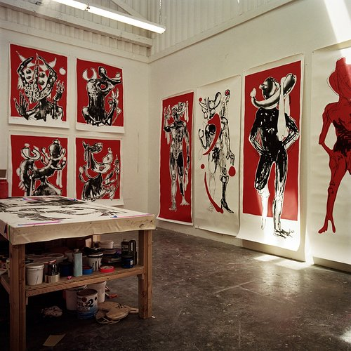 artist studio with large red paintings on the walls