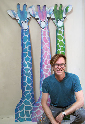 man in front of three giraffe artworks
