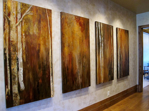 Four large paintings of trees with orange and brown colours