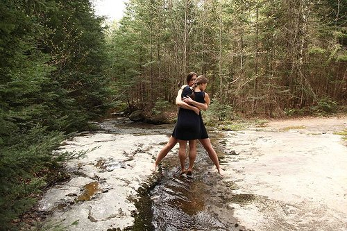 A photo of two people embracing while standing over an icy stream in the forest