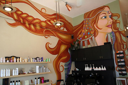 A wall mural in a hair salon, depicting a woman with long, flowing hair