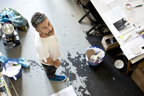 Artist Pierre Huyghe looks up at a camera in his white, brightly lit studio