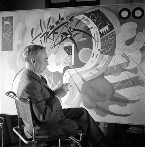 An old black and white photo of Wassily Kandinsky working on a painting