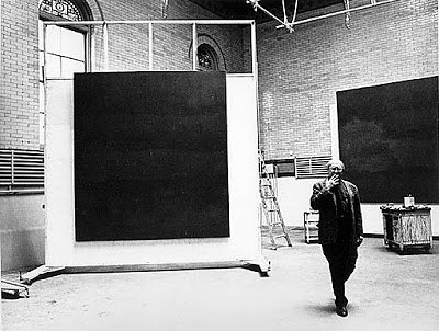A black and white photo of Mark Rothko standing next to a large monochrome in his studio