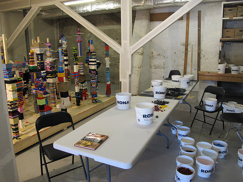 A studio space with several buckets filled with legos, and on the opposite side, a lego sculpture