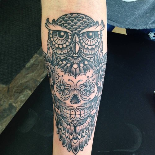 A black and white tattoo of a stylized owl