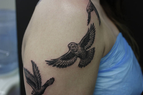 A shoulder tattoo of three owls in flight