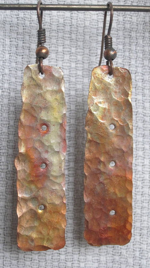 A pair of dangly earrings with rough, rectangular pieces of material