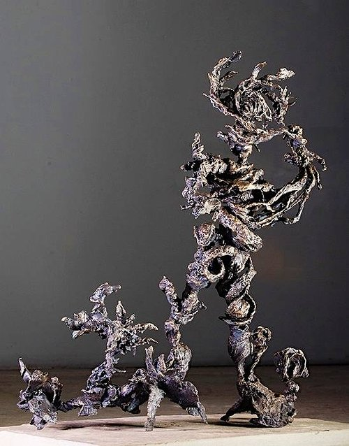 A series of tree or figure-like abstract bronze sculptures