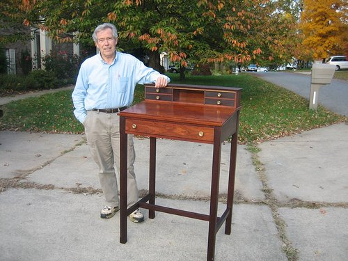 A photo of the artist next to a rosewood desk of his construction