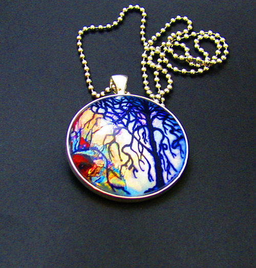 A glass jewelry pendant with a watercolour-like tree design