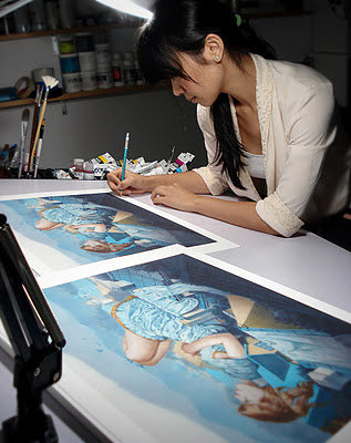 An image of Tran Nguyen working at her drawing table