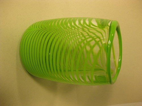 An abstract work of glass with lime green stripes