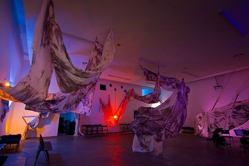 A photograph of an installation in a room featuring large sheets of fabric and coloured lights