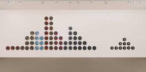 A wall installation of 67 elk-hide drums painted to look like LPs