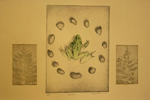 An intaglio print of a frog sitting in a circle of stones