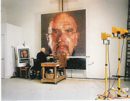 A photograph of Chuck Close working on a painting