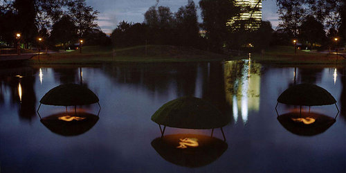 An image of several lanterns mounted to float above a body of water