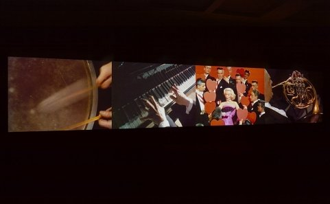 A photo of a four-channel video projection of different music artists