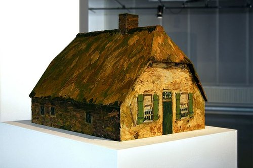 A small sculpture of a house, painted to look like an oil painting