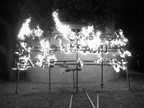 A black and white photo of letters on a wire frame burning