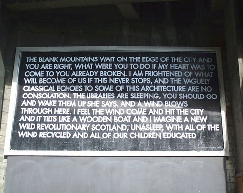 A photo of a lengthy poem in block letters on a black billboard