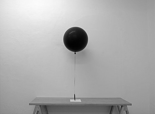 A photo of a black balloon floating above a table