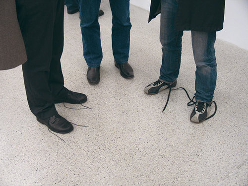 A photo of several people with their shoelaces untied
