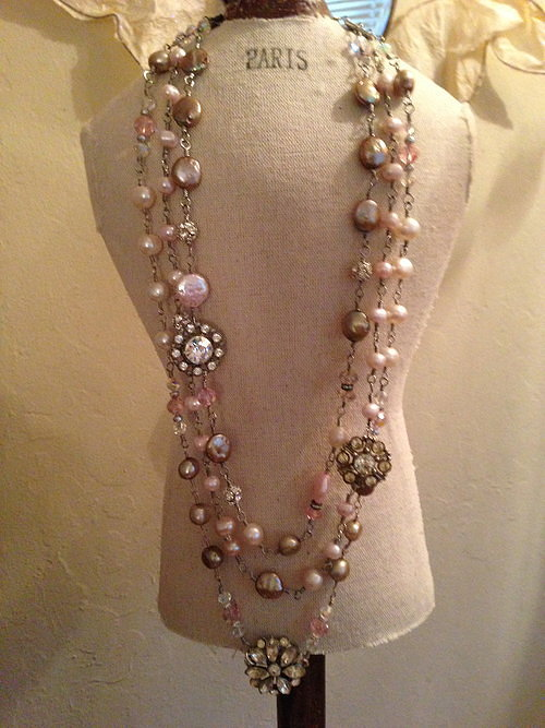 A complex handmade necklace shown on a mannequin