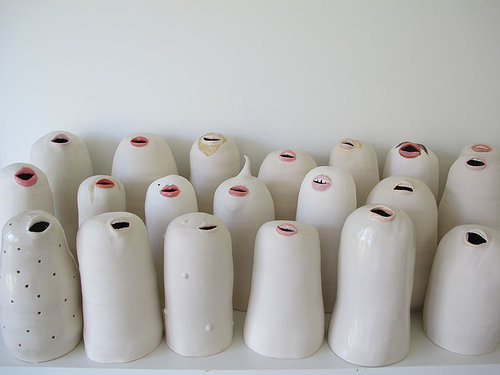 A series of ceramic money banks with the coin slots formed to look like mouths