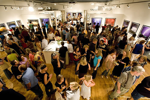 A photo of a crowd of people at an art opening in a gallery