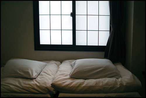 A photo of two pillows against a wall in an empty bedroom in Japan