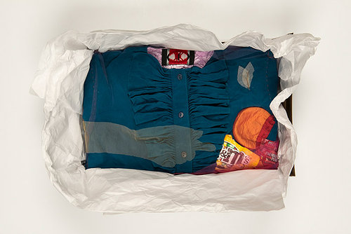 A piece made of a folded-up shirt in a box, with some candy wrappers