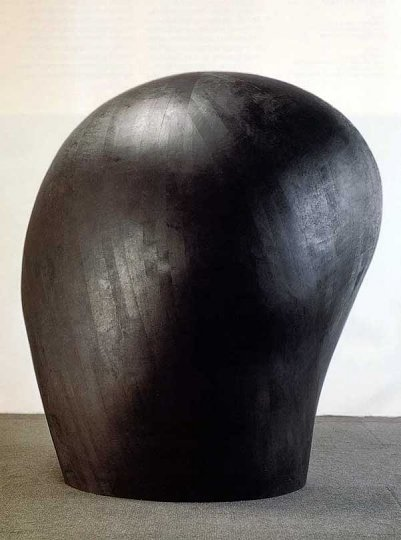 A large bulbous wood sculpture painted black
