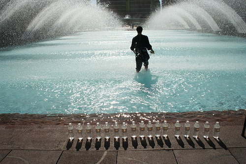 A performance still of a man walking into a fountain