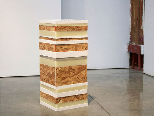 An image of a stack of wax and particle board squares that create a square column