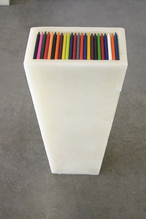 A tall wax stand full of wax crayons