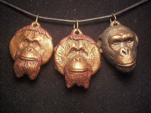 A set of three pewter pendants in the shape of the faces of great apes