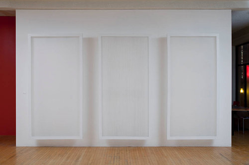 A series of three artworks that look like white monoliths in white frames