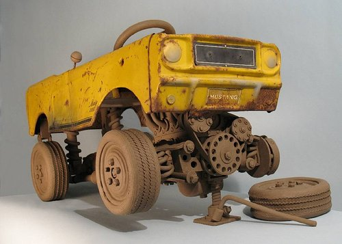 A sculpture composed of a gutted Mustang car body with replacement parts made of clay