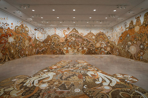 An installation view of an earth-coloured drawing on the walls of a gallery