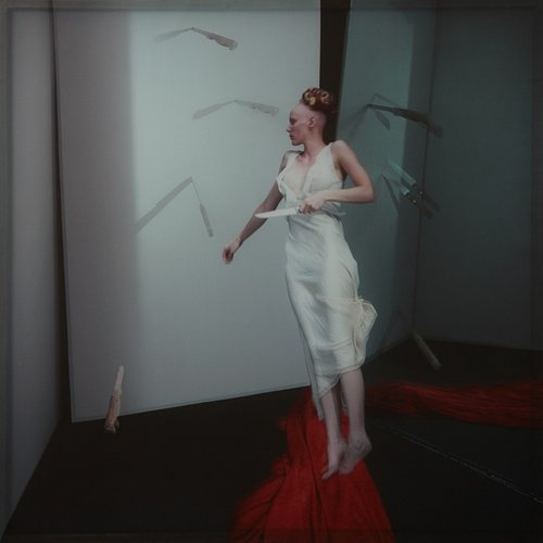 A printed photograph of a woman dodging throwing knives in a dream scenario