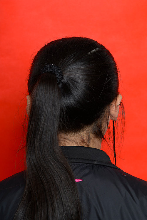 A photo of the back of a young Chinese girl's head, on a red background