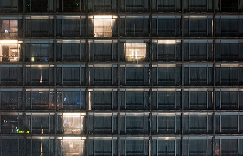 A photo of a wall of windows on the exterior of an apartment building, some lit, some dark